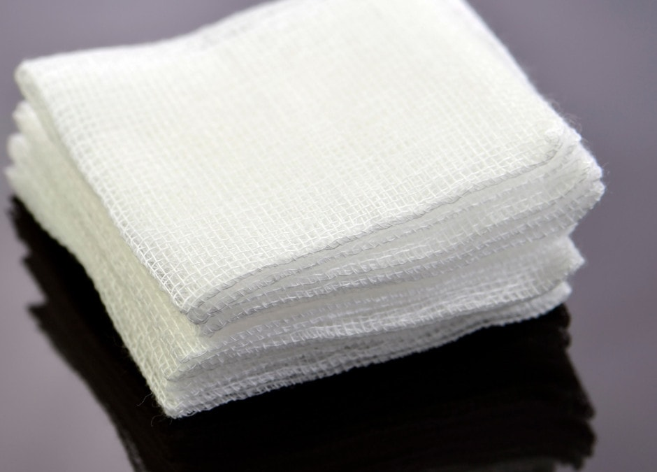 A stack of 4x4 gauze pads laying on a dark table