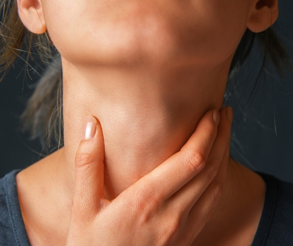 Up close picture of a womans neck being held by her hand as if it is sore or hurting